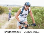 Fit attractive couple cycling on mountain trail on a sunny day - stock photo