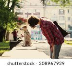 Stock photo woman walking with a pet in the city park 208967929