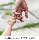 child holds the finger of a... | Shutterstock . vector #209117530