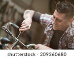 young man working in a biking... | Shutterstock . vector #209360680
