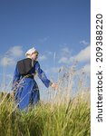 Small photo of A low angle view of an Amish girl walking in a field touching the grass