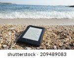 e book reader on a beach with... | Shutterstock . vector #209489083