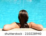 Back view of relaxed woman in swimming pool with blue water - stock photo