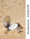 Old pocket watch in sand - stock photo