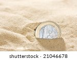 Euro coin in the sand - stock photo