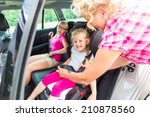 mother buckling up on child in... | Shutterstock . vector #210878560