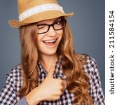 Small photo of portrait of a smiling young woman with casual garb winking and giving a thumbs up