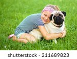 Stock photo little girl and her pug dog on green grass outdoor shoot 211689823