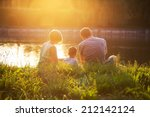 Family Resting At Sunset In Th...