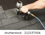 new roof shingle being applied   Shutterstock . vector #212157436