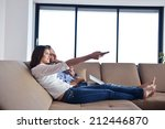 couple on sofa with tv remote | Shutterstock . vector #212446870