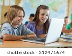 boy and girl using a laptop at... | Shutterstock . vector #212471674