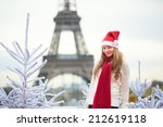 Girl in Santa hat near the Eiffel tower in Paris during Christmas time - stock photo