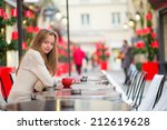 Girl sitting in a Parisian cafe at Christmas time - stock photo