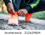 young woman tying laces of... | Shutterstock . vector #212629804