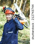Small photo of Portrait of lumberjack logger worker in protective workwear with chainsaw at forest