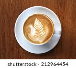 Cup of coffee latte with leaf design art in froth, on a wooden table and viewed from top. - stock photo