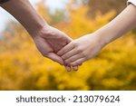 couple holding hands in park...   Shutterstock . vector #213079624