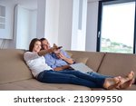 couple on sofa with tv remote | Shutterstock . vector #213099550