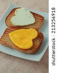 Small photo of Albumen and egg yolk as a heart on a toast