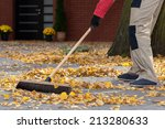 A Man Sweeping Leaves From His...