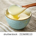 bowl and spoon of vanilla sauce | Shutterstock . vector #213608113