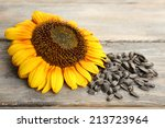 Sunflower And Seeds On Wooden...