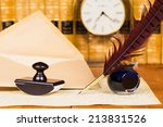 Small photo of Quill and ink with antique books in the background