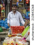 Small photo of Mumbai, India - August 28, 2014 -Man selling colorful coth for dressing Ganesha god for worshiping on the first day of Ganesha Chaturathi