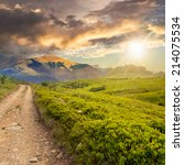 gravel road going off into the distance and passes through the green field in mountains at sunset - stock photo