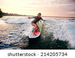 Young Woman Surfboarding At...