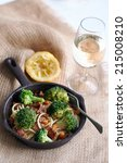 Meal in a pan : Broccoli, almonds, bacon, noodles with lemon and glass of water - stock photo