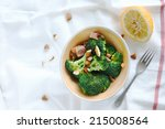 A lunch of broccoli, almonds and bacon with lemon - stock photo
