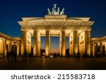 Stock photo the floodlit brandenburg gate in berlin with a few fleeting shadows of anonymous berliner s 215583718