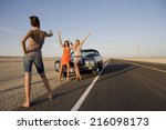 Young woman taking photograph of friends by car on open road, low angle view - stock photo