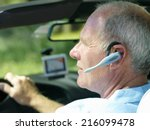 Small photo of Man with hands-free device in car, side view