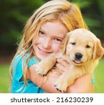 Stock photo adorable cute young girl with golden retriever puppy 216230239