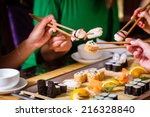 young people eating sushi in... | Shutterstock . vector #216328840