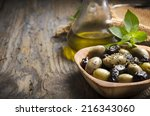 olives and olive oil on rustic... | Shutterstock . vector #216343060
