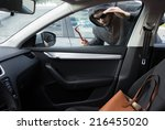 Thief is looking for unattended valuables left in a car - stock photo
