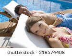 couple laying on lounge chairs... | Shutterstock . vector #216574408