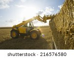 Tractor Loading Straw Bales...