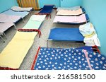 Small photo of Rollaway beds and cots in brightly colored dormitory of a nursery