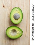 whole and half avocado on wood... | Shutterstock . vector #216893620