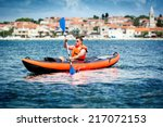 young men paddle a kayak on the ... | Shutterstock . vector #217072153