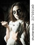 Small photo of Horror style shot: a scary monster girl with moppet doll and needle in hands