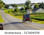Amish Buggy Goes Down Road In...