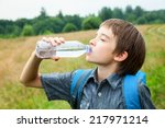 boy drinking water from pet... | Shutterstock . vector #217971214