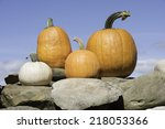 Four Pumpkins Atop A Stone Wall ...