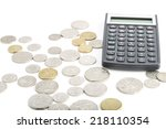 Coins placed on a white background with a calcultor on the background - stock photo